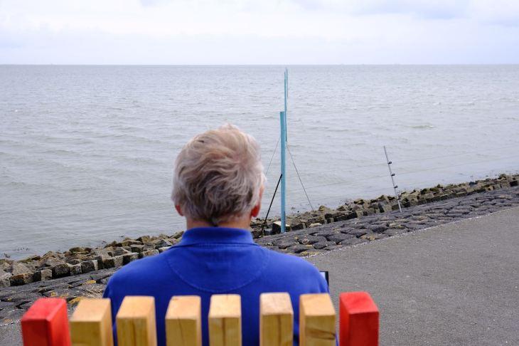 Vanuit de wadden zee zijn de palen zichtbaar die de verwachte waterhoogte in de 22e eeuw visualiseren